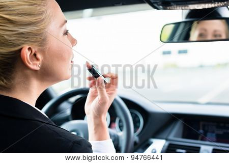 Woman using lipstick while driving her car