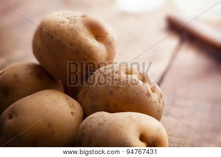 Fresh harvested potatoes spilling out of a burlap bag, on a rough wooden palette. Shallow depth of field.