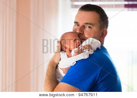 Father cuddling crying baby girl on arm