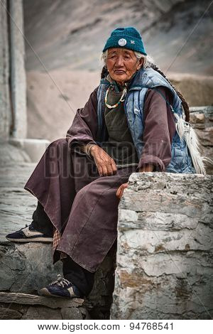 LAMAYURU, INDIA - SEPTEMBER 10, 2011: Old Tibetan woman sitting near Lamayuru  gompa in Ladakh, India