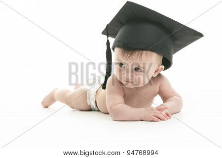 Portrait of a sitting baby with a graduation cap