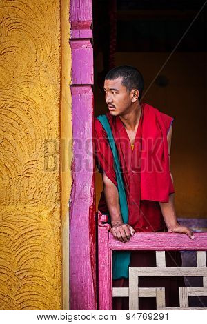 THIKSEY, INDIA - SEPTEMBER 13, 2012: Young Buddhist monk standing in doorway of  of Thiksey gompa, Ladakh, India