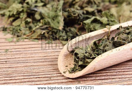 Dried Nettle With Spoon On Wooden Surface