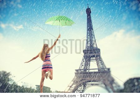 Beautiful Girl Running With An Umbrella In The Rain On A Background Of The Eiffel Tower. Summer Trip