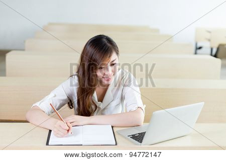 Asian  beautiful female student study with laptop in classroom