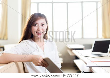 Asian beautiful female student study in classroom with tablet