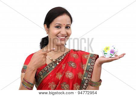 Excited Indian Woman Holding A Piggy Bank