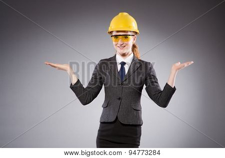 Female engineer with helmet isolated on gray