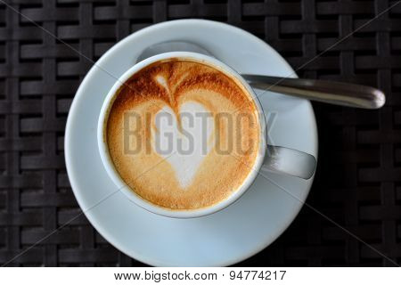 Cup of foamy cappuccino on a black background