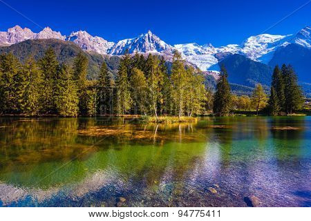 The snow-covered Alps and evergreen fir-trees are reflected in lake. Early fall in Chamonix, Haute-Savoie. France