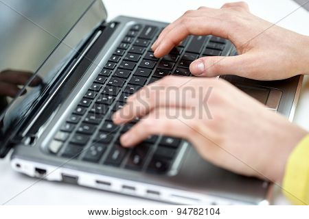 business, technology, school, people and education concept - close up of businesswoman or student girl with laptop computer sitting at table