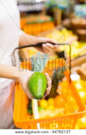 sale, shopping, consumerism and people concept - close up of young woman with food basket and avocado in market
