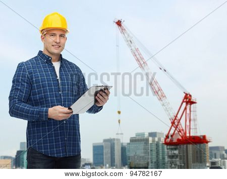 repair, construction, building, people and maintenance concept - smiling male builder or manual worker in helmet with clipboard over city construction site background