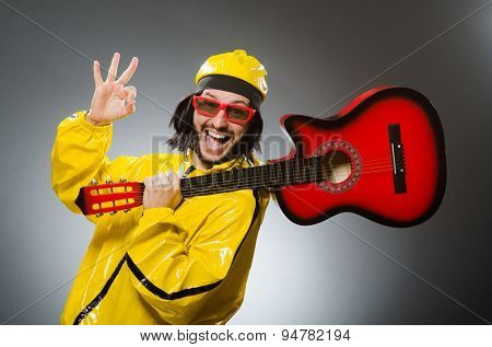 Funny man wearing yellow suit and playing guitar