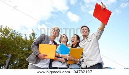 education, friendship, future and teenage concept - group of happy students with folders pointing finger at campus or park