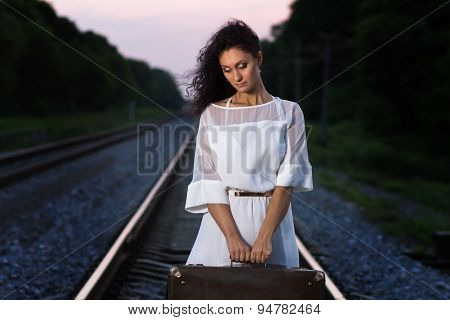 Young Beautiful Sad Woman With Suitcase At The Railroad