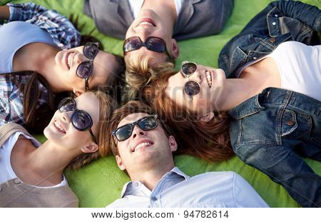 summer holidays, friendship, leisure and teenage concept - group of students or teenagers lying in circle at campus or park