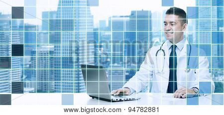 medicine, profession, technology and people concept - smiling male doctor sitting at table with laptop and stethoscope over city and blue grid background