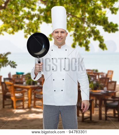 cooking, profession and people concept - happy male chef cook holding frying pan over restaurant lounge on beach