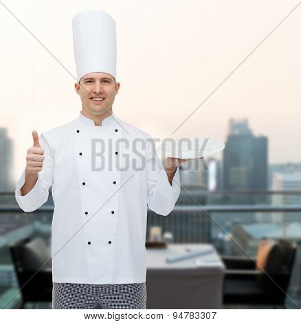cooking, profession, advertisement and people concept - happy male chef cook holding something on empty plate and showing thumbs up over city restaurant lounge background