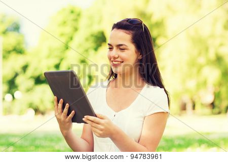 lifestyle, summer, vacation, technology and people concept - smiling young girl with tablet pc computer sitting on grass in park