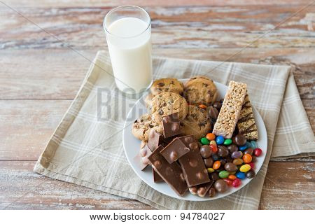 junk food, sweets and unhealthy eating concept - close up of candies, chocolate, muesli and cookies with milk glass on plate