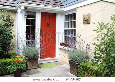 Charming colorful front door entrance with blooming lavender in containers.