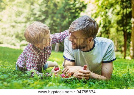 Summer photo happy father and son together lying on green grass