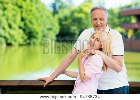 Portrait of an happy mature couple in front of a lake