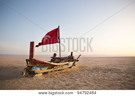 Abandoned colourful Boat in desert at dawn. Tunisia