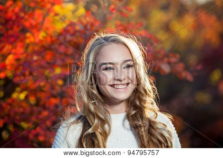 beautiful young woman with curly hair against a background of red and yellow autumn leaves, happines
