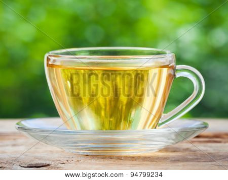 Tea Cup On Wooden Table. Green Background.