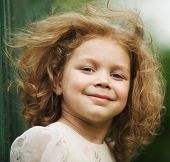 foto of girlie  - Happy beautiful cheerful curly little girl in a dress - JPG