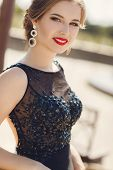 image of wearing dress  - Brown-eyed brunette,a beautiful young woman with bright red lipstick on her lips,stylish makeup,elegant fashionable hair style in the ears wearing earrings,wearing a black dress,posing for the photographer in a small town in the summer outdoors ** Note:  - JPG