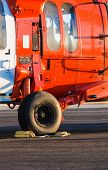 stock photo of military helicopter  - Orange military helicopter at the airport closeup - JPG