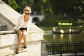picture of beautiful senior woman  - Beautiful young woman sitting in the Park near the lake - JPG