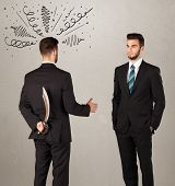 pic of backstabbers  - Ruthless businessman handshake with a hiding weapon and drawn curly lines around his head  - JPG