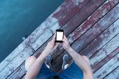 foto of pov  - POV of young man relaxing on the dock near the river and checking his telephone. High angle shot Selective focus.