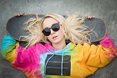 pic of nose ring  - Blond skater girl laying down with board - JPG