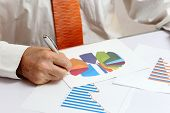 picture of anal  - businessman is writing on different documents with graph - JPG