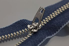 stock photo of zipper  - studio photography of blue zipper opened on a half to a gray surface - JPG