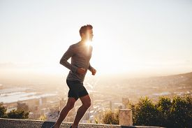 stock photo of morning sunrise  - Young man training in the nature with sun behind him - JPG