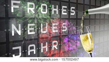 Champagne pouring against new year message on black roller board in german