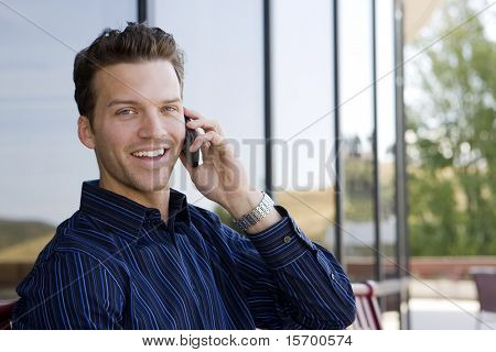 Attractive business man on his cell phone outside an office building