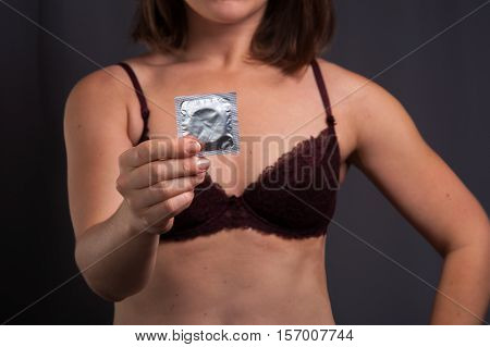 Sexy woman in lingerie holding condom in hand. Sexual contraception safety sex concept.