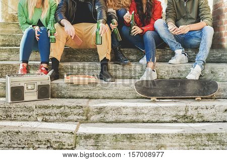 Close up of group of young people hands toasting beer and having fun outdoor - Fashion buddies sitting in staircase socializing - Concept of relaxation with friends - Main focus on left man hands