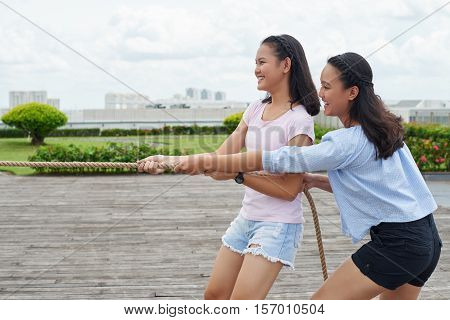 Side view of happy sisters enjoying playing tug of war