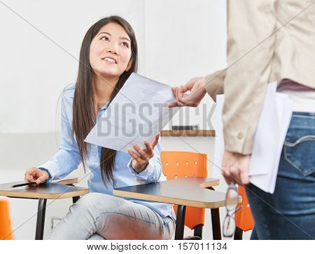 Girl taking a test in high school supervised by her teacher
