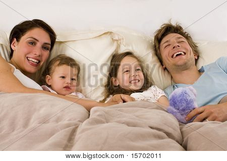 Happy young family laying in bed
