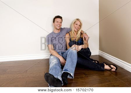 Attractive young couple sitting in their new home